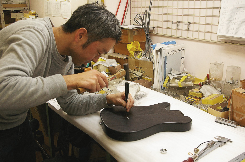 Long time friend and luthier Aki is carefully mounting the string ferrules on the T-Wave body.