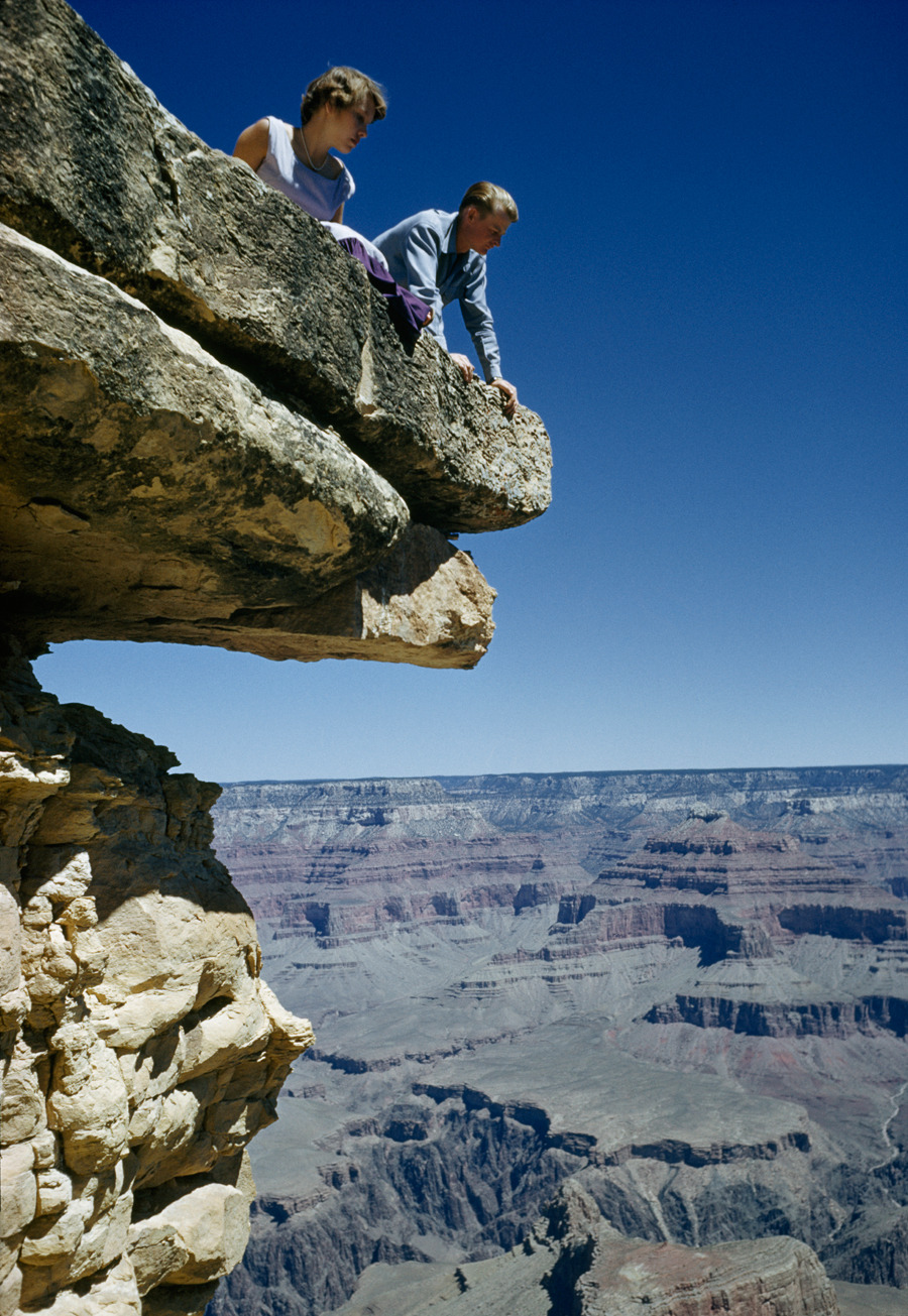 A young couple peers over the edge of Hopi Point into the Grand Canyon, May 1955.Photograph by Justin Locke, National Geographic