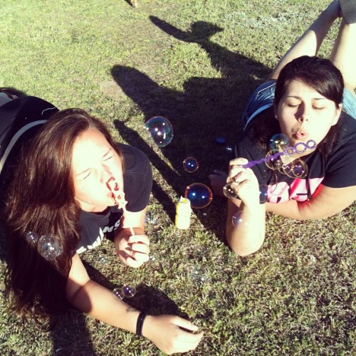 Blowing bubbles in the grass with my twin ❤ @caralucas10