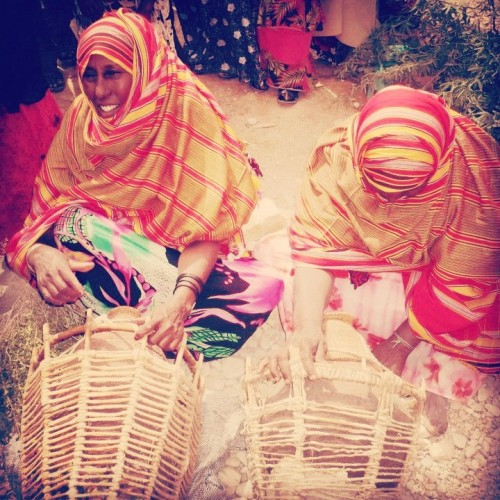 "dynamicafrica:  nomadfawzi:  Somali women, wearing the infamous orange & red ""Alindi"" fabric made in Somalia. The women are weaving a baskets around a milk/water containers. This basket will, later on, be attached on to a camel. The main purpose of weaving this kind of basket is to protect the fragile clay pot — containing valuable liquids like water and milk —thus, it will act like a crash-helmet. Also, the woven basket provides handle points for the container, so that it can be conveniently carried by hand, or attached to the camel.  Why is it infamous?"