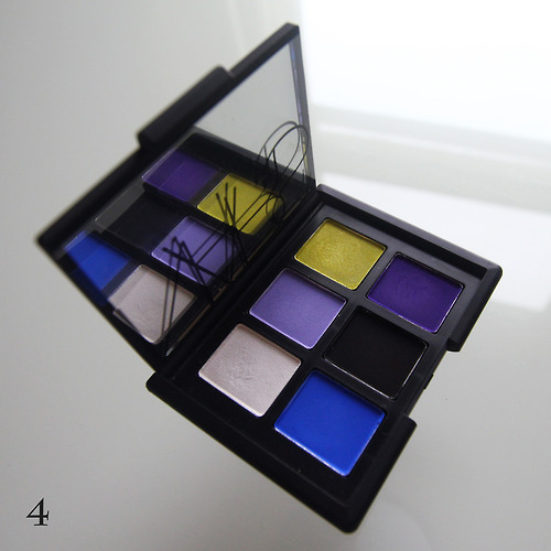 federov:  NARS New Wave I bought this palette for working with eyeliner and that's how I usually use it - I can set the line, enhance it with color and/or add a soft, smudgy effect. Both the black and white shades - also sold as the Pandora duo - are satiny. This is not evident from looking at them in the pan, but it's a nice surprise because it makes them more wearable and less like chalk/charcoal. The bright blue (Outremer), dusty violet (Jolie Poupée) and royal purple (Daphne) are all matte and the lime green (Rated R) has a bit of shimmer. Where to start with these colors.  Even though it's soooo pretty in the pan, I've never figured out how to use Rated R because it gives my skin a sickly yellow tone. Maybe someday? Meanwhile, Daphne is difficult to work with. Will not blend without dissolving, will not build evenly. It works best in tandem with eyeliner, patted down over a very small area. It makes a fantastic smudgy purple lash line, though, so I actually use it all the time.  Jolie Poupée and Outremer are easier to love. The versatile gray-purple is definitely a color and not a neutral, but it wouldn't be difficult to wear if you're used to neutrals. Outremer, on the other hand, is not even remotely neutral. It applies completely true-to-pan electric blue. New Wave is counterintuitively versatile. The black and white are good basic shadows for all your smudgy, smokey eye needs and they pair very well with the bright accent colors.  (part 4 of 6)