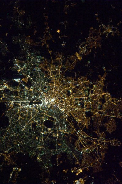 "blech:  Berlin at night from space, with the old west and east still visible:  ""Berlin was divided into two parts for over 40 years,"" explains Christa Mientus-Schirmer of Berlin's city government. ""And although we've made a lot of progress in the 20 years since the wall fell, we haven't had the money we would have liked to equalise the two parts of the city."" Daniela Augenstine, of the city's street furniture department, says: ""In the eastern part there are sodium-vapour lamps with a yellower colour. And in the western parts there are fluorescent lamps – mercury arc lamps and gas lamps – which all produce a whiter colour."" The western Federal Republic of Germany long favoured non-sodium lamps on the grounds of cost, maintenance and carbon emissions, she says.  Guardian quote via chriswoebken."