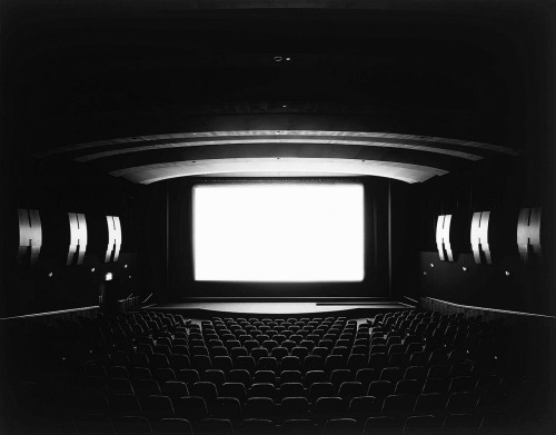 "Hiroshi Sugimoto - Theaters (1978-93) Artist's statement:  ""I'm a habitual self-interlocutor. Around the time I started photographing at the Natural History Museum, one evening I had a near-hallucinatory vision. The question-and-answer session that led to this vision went something like this:  Suppose you shoot a whole movie in a single frame?  And the answer: You get a shining screen.  Immediately I sprang to action, experimenting toward realizing this vision. Dressed up as a tourist, I walked into a cheap cinema in the East Village with a large-format camera. As soon as the movie started, I fixed the shutter at a wide-open aperture, and two hours later when the movie finished, I clicked the shutter closed.  That evening, I developed the film, and the vision exploded behind my eyes."""