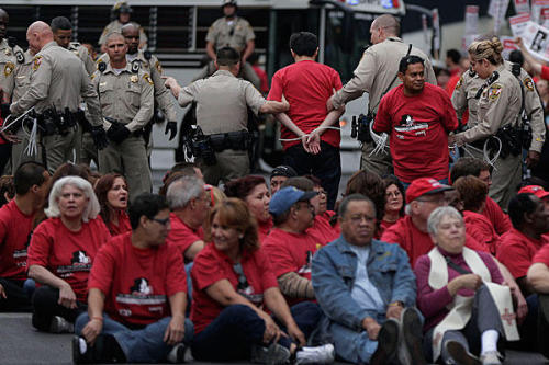 "98 arrests in Las Vegas casino union protest; first time union members deploy civil disobedience outside a unionized casino in more than two decadesMarch 21, 2013 Throngs of workers blocked traffic on the Las Vegas Strip Wednesday in a demonstration against the Cosmopolitan casino that ended with the arrest of nearly 100 protesters. Police led workers wearing red union shirts one-by-one into a white police bus. Police arrested 98 protesters, according to Metro Police Capt. Todd Fasulo. The workers chanted, ""If we don't get no contract, you don't get no peace,"" as they waited to be taken away. Las Vegas' largest and most powerful union has been in contract talks with Cosmopolitan Las Vegas owner Deutsche Bank for two years. Earlier this year, the 54,000-member union held two one-day pickets outside the casino, which sits on a bustling corner in the heart of the tourist corridor. They marked Culinary Workers Local 226's first pickets on the Strip since 2003. Wednesday's action was the first time union members deployed civil disobedience, the tactical use of nonviolent law breaking, outside a unionized casino in more than two decades, according to union spokeswoman Yvanna Cancela. Protesters shut down rush hour traffic for more than an hour in both directions on the block that is also home to the Bellagio, Aria and Planet Hollywood casinos. Cancela estimated the crowd at about 1,500 people. Talks with the Cosmopolitan have stalled on a range of issues, including wages, health care and job security, as Cosmopolitan casino refuses to pay its employees fair wages. The 2-year-old Cosmopolitan was built by the German investment bank after its original developer defaulted. It is one of just a handful of non-unionized casinos on the Strip, along with the Venetian, the Hard Rock Hotel and Casino, and the Palms. A majority of Cosmopolitan service workers signed cards in 2010 saying they wanted representation. On Wednesday, protesters said they were worried that Deutsche Bank was stalling because it intends to sell the casino and doesn't want to be burdened by a union contract. Source"