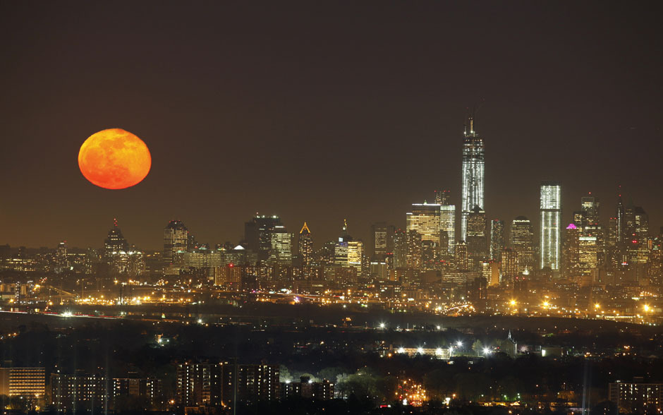 A full moon rises over the skyline of New York next to One World Trade Center in Lower Manhattan, as seen from the Eagle Rock Reservation in West Orange, New Jersey, April 26, 2013.  REUTERS/Gary Hershorn