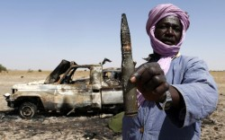 fotojournalismus:  A Tuareg man holds a bullet near a destroyed vehicle belonging to Islamist rebels on the road between Diabaly and Timbuktu in Mali on January 30, 2013. [Credit : Benoit Tessier/Reuters]