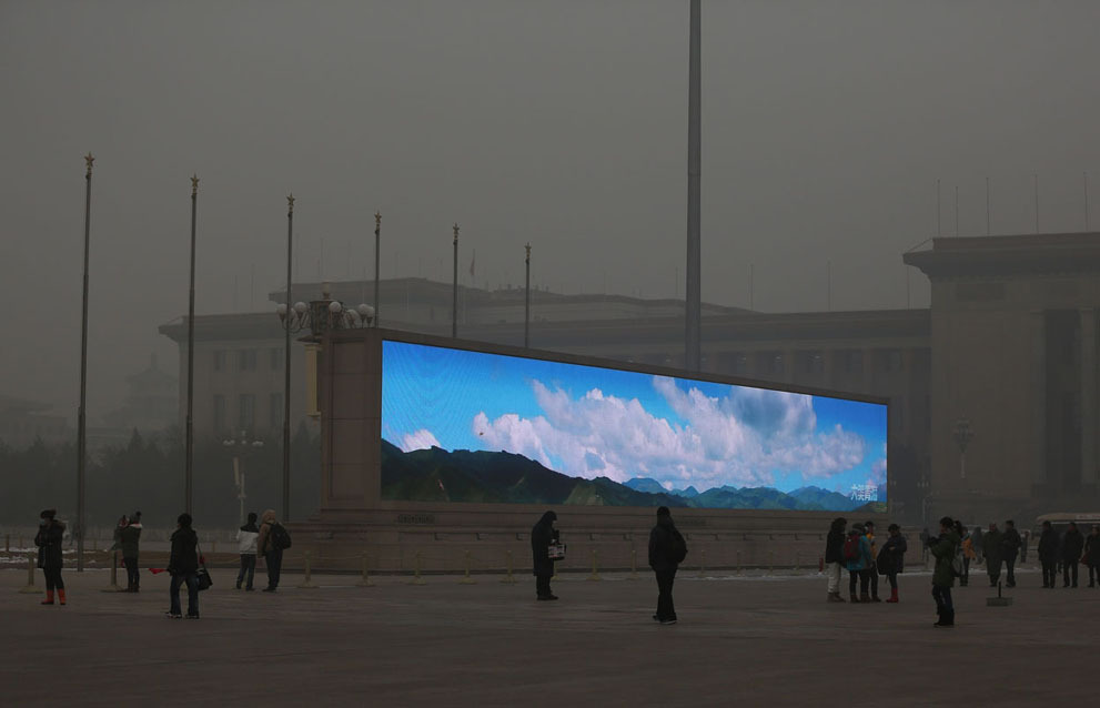 A bright video screen shows images of blue sky on Tiananmen Square during a time of dangerous levels of air pollution, on January 23, 2013 in Beijing. (Feng Li/Getty Images)