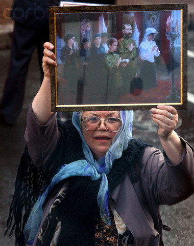 A Russian woman demonstrates a picture, showing the praying Tzar's family, as she left a church service devoted to the reburial of the Russian Empress Maria Feodorovna , in St.Petersburg, Thursday 28 September 2006. Danish princess Dagmar, which became Russian Empress Maria Feodorovna, as a wife of Russian Emperor Alexander III, escaped Russia after the October Bolshevik revolution and died in Denmark. Maria Feodorovna was reburied in Peter and Paul Cathedral in St. Petersburg near her husband.