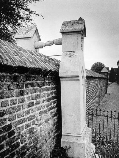 "Grave of a Catholic woman and her Protestant husband. The Protestant Colonel of Cavalry, JWC of Gorkum married the Catholic damsel JCPH of Aefferden. This ""mixed"" marriage, at that time (the 19th century), would have given them trouble. The wife wanted to be buried next to her husband, but the difference in their denomination would not allow that. So the Colonel was buried in the Protestant part, against the separation wall and his wife was buried on the Catholic side."
