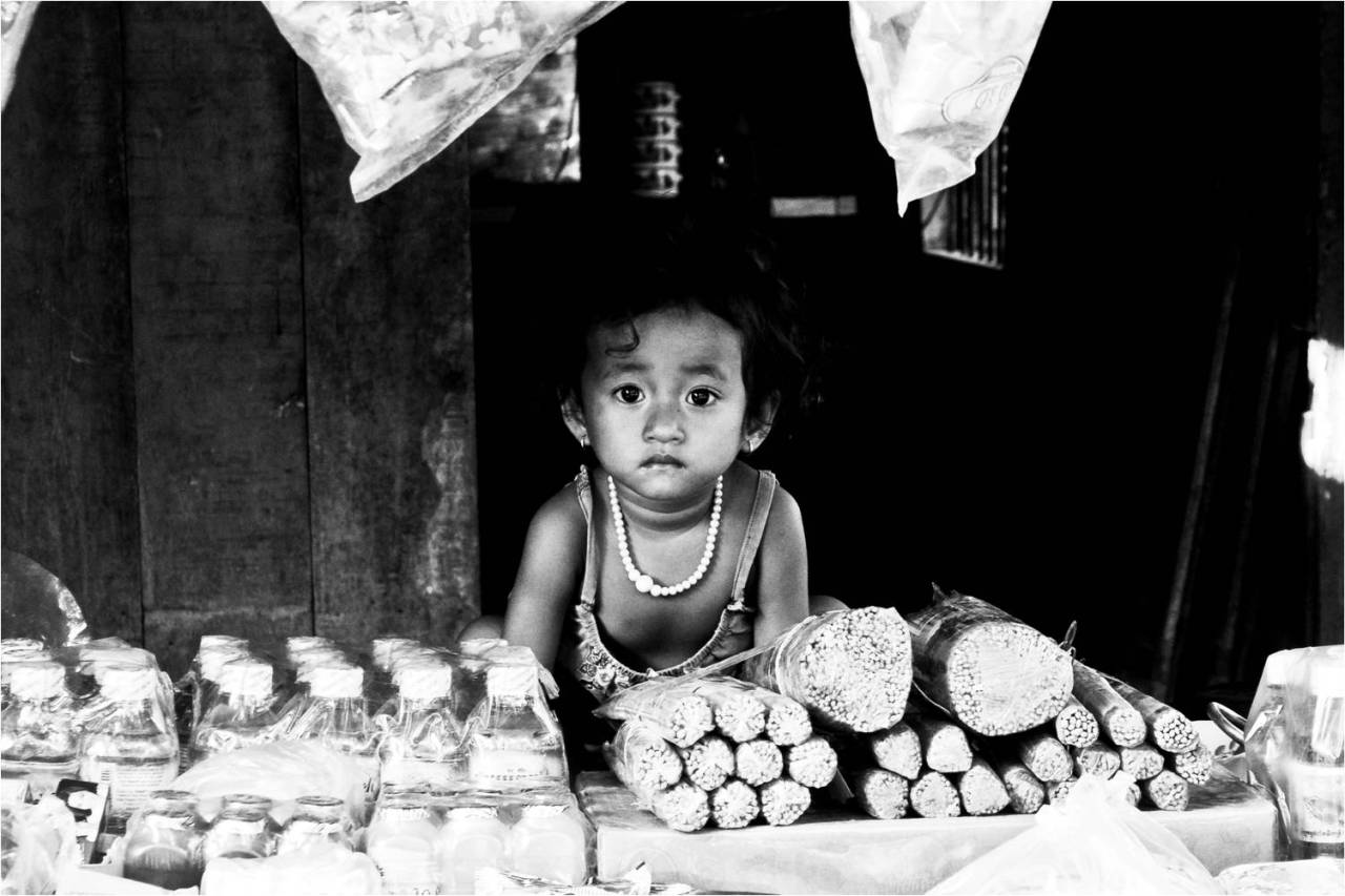 A child staring out of roadside shop in Takeo, Cambodia