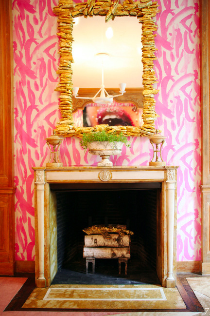 The illustrative pink watercolor wallpaper takes this fireplace from predictable to exotic for an affair or the heart.