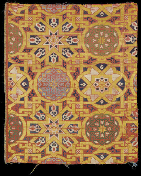purplefigtree:  Lampas-weave silk, Spain, 14th century.   The pattern, which appears continuous, has been adapted to the system of 'repeats' needed to produce a textile. Each design unit contains an eight-pointed star, a quatrefoil and two roundels. The compartments they form are filled with a variety of smaller motifs, from interlace patterns in green or blue to tiny knots and fleurs-de-lis. Textiles with geometrical interlace of this type were mainly produced in southern Spain and North Africa. This example was probably made in south-west Spain in the 14th century, perhaps in Granada, which was the capital of the Muslim Nasrid dynasty from about 1232 to 1492. Such silks were not only used in Spain. They seem also to have been popular in Italy. This piece formed part of a hanging behind a large wooden statue of the Virgin Mary in Florence. It was bought there in the 19th century. (V&A)