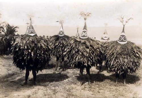 oakapples:  Duk-Duk dancers in New Britain, 1913. Duk-Duk is a male-only secret society that operates among the Tolai people of New Britain, the largest island in Papua New Guinea's Bismarck Archipelago. Members of the society are followers of a mysterious spirit (Duk-Duk) who wears leaves around his body and a tall, conical mask. The entrance fee to the society traditionally consists of a string of cowrie shells threaded on strips of cane, often 100 m or more in length. Duk-Duk appears only with the full moon, when festivals and ceremonies are celebrated in secrecy; strangers are excluded from these rituals on pain of death. The followers of Duk-Duk have dwindled in number through the 20th century, but a few still remain in this isolated corner of the world.