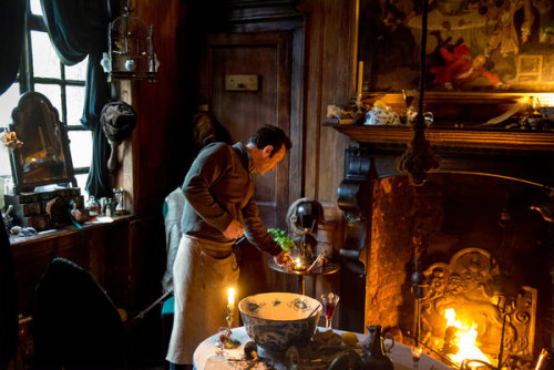 David Milne, curator of the Dennis Severs' House Museum, lights candles at the museum, on Folgate Street