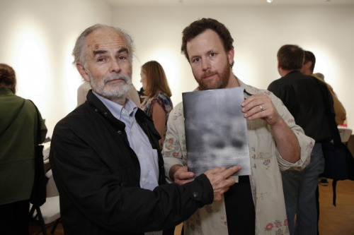 "americanphoto:  This photo shows photographer John Gossage and bookseller Harper Levine touching a book at last year's 10×10 Japanese Photobooks event. It's back this year in a new, American incarnation, and I'm wondering what this means about our relationship to technology: ""After a rush to all things digital, it seems only natural that photography audiences would ""return"" to the physicality of books, and celebrate them in intimate gatherings like 10x10, or the book meetups that I sometimes hear about. Perhaps these gatherings are more significant than the books themselves—after all, you can look at photobooks until your eyes bleed on those crazy websites! I can't really explain this here, but sometimes I'm convinced that our Facebook-centric model of online interaction, which seems as codified as ever, has actually made it more difficult to meet people through the internet—IRL, that is. This is an important task of technology, and we shouldn't feel any shame about asking the not-yet-forgotten book to pick up the slack."""