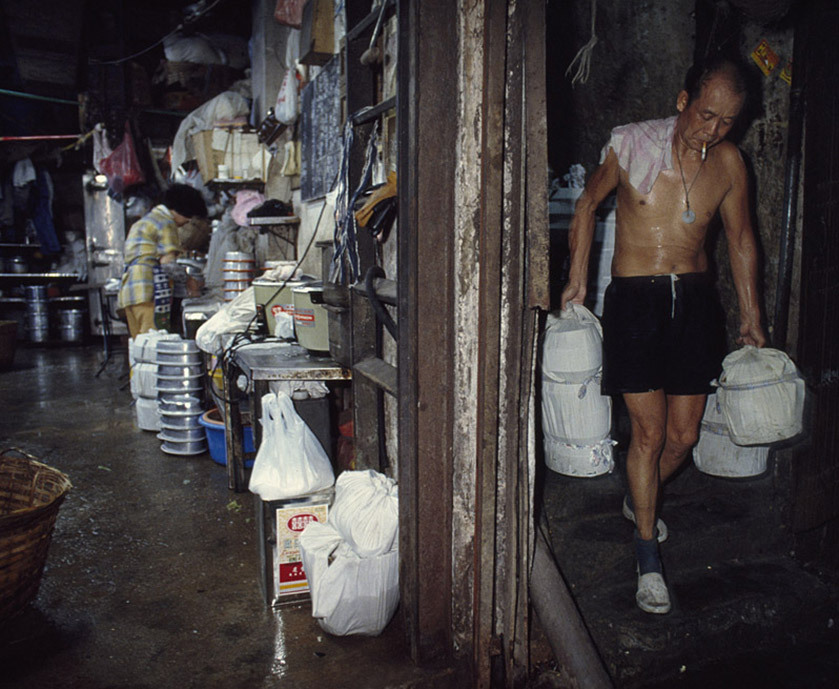 """Walking into the city, you found narrow alleys between the buildings with dripping pipes overhead, discharge flowing in gutters, people stripped to the waist in their underwear working in tiny factories, the sound of metal pounding metal, butchered animals, unlicensed dentists, a two-man rubber plunger factory, carts stacked with steaming food, everything mixed together. It felt unreal (especially in the early days), and yet totally normal to everyone living and working there."" —Photographer Greg Girard, on life inside the City of Darkness."