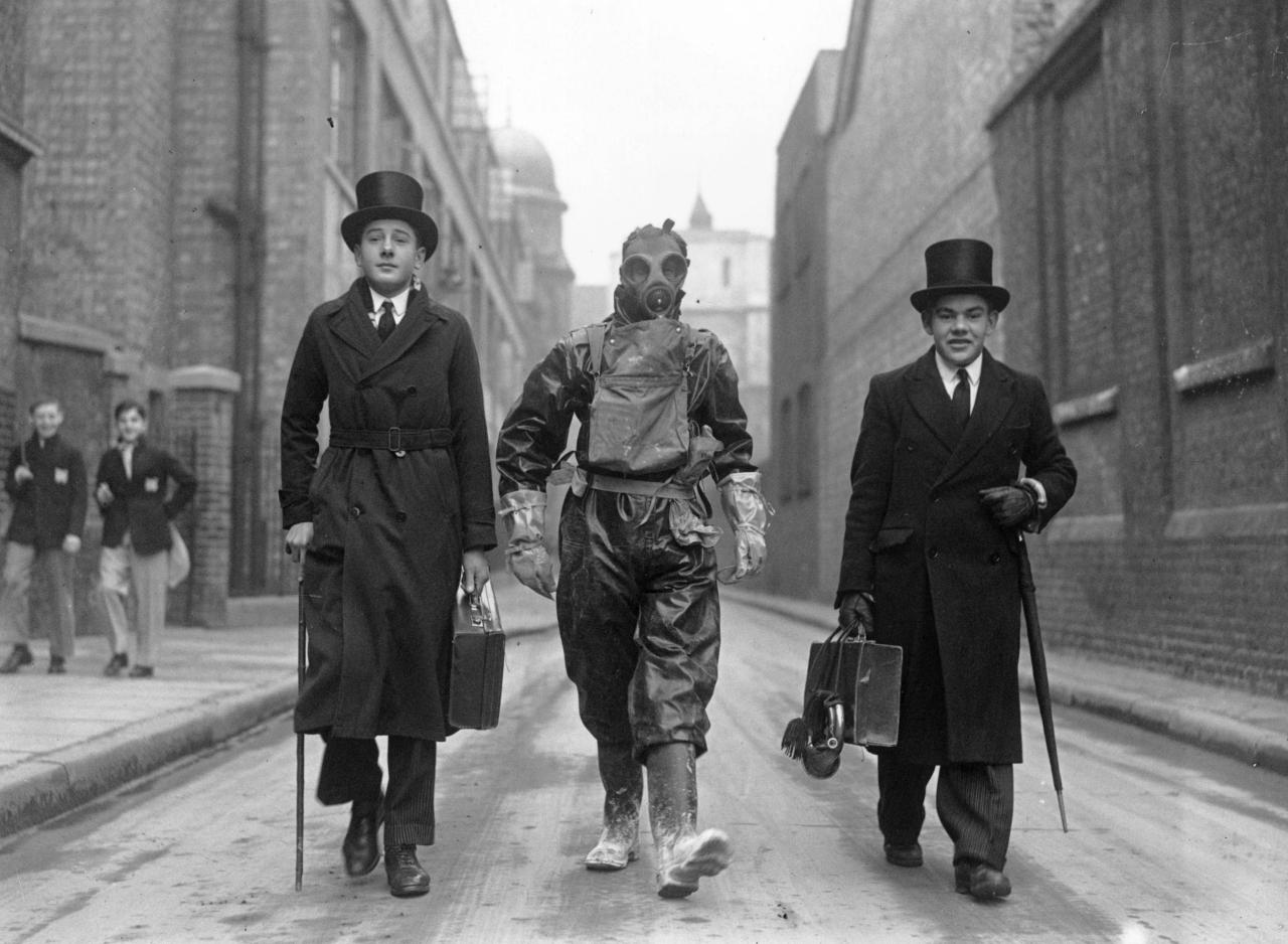 Westminster schoolboys heading off to school with an employee of the Westminster City Council taking final exams in an anti-gas course. 5 February 1938