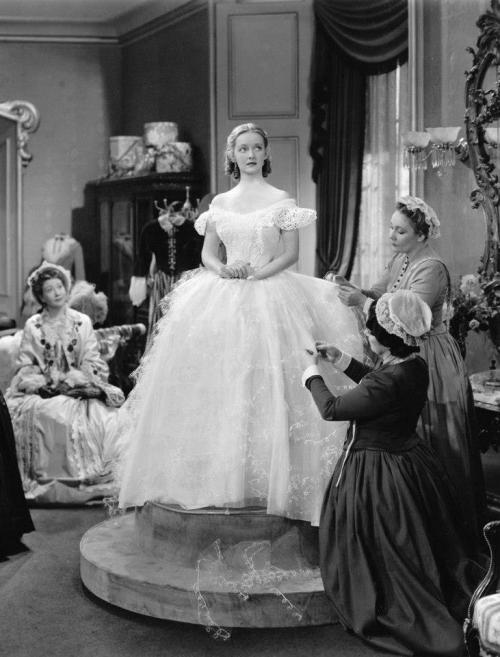 Jezebel - Bette Davis as Julie wearing an off-shoulder ballgown with corseted bodice and embroidered tulle overlay.