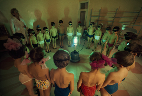 natgeofound:  Children circle around an ultraviolet lamp to get a dose of vitamin D in Murmansk, Union of Soviet Socialist Republics, August 1977.Photograph by Dean Conger, National Geographic