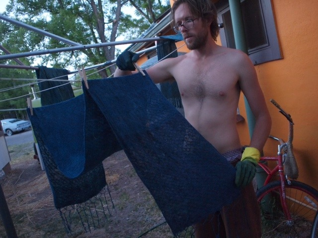 Kyle hanging up his tussah silk shawl just after dipping it in the Indigo.