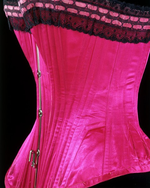 "omgthatdress:  Corset 1890-1895 The Victoria & Albert Museum ""Improvements in design, equipment and materials meant that corsets could mould the figure to suit the latest fashions. The straight busk on this corset creates a vertical line from bust to abdomen which complemented the less rounded, more angular silhouette of the 1890s. It was also supposed to relieve pressure on the internal organs while supporting the stomach. Shaped pieces (five on each side) have been seamed together and bust and hip gussets inserted to give the corset its distinctive shape. Strips of whalebone follow the contours of the hourglass silhouette, creating a rigid structure to emphasise the smallness of the waist. Each strip is enclosed in a bone channel formed by neat rows of machine stitching. The decorative embroidery stitches (flossing) visible towards the bottom and back of the corset prevent the whalebone from forcing its way out of these channels. A hook is attached at the centre front to prevent the petticoat from riding up and causing extra bulk at the waist."""