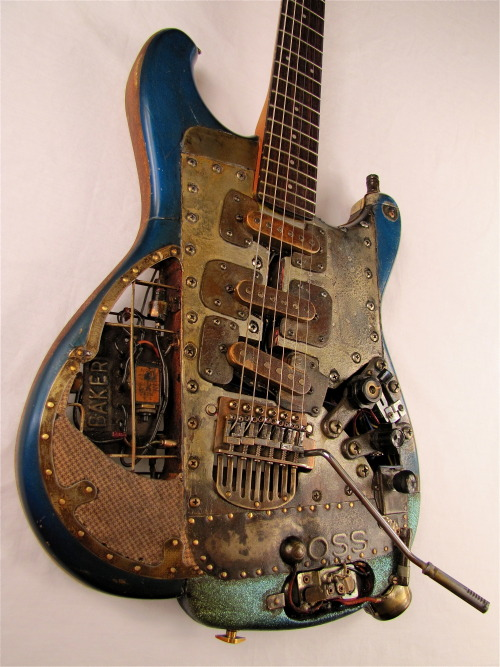 "OSScaster Electric Guitar by Tony Cochran Guitars This is the only electric guitar in existence where both an OSS device and a Tone Baker have been electronically mated successfully. Buckle up, guitarionados, this instrument is a rough old relic but its story is almost unbelievable. Osso Bucca was an immigrant who came to America in the '60s after being fired by Galanti Guitar in Italy. He brought his knowledge of ""radio gain"" (that's how it translates to English) with him to Wyoming. There he met up with Tex Gilders who had been fired by Fender for working on a device of his own, called a ""Baker"". It's not real clear what either of these devices is supposed to do singularly but, supposedly, they do it way better in tandem. The only quote from Gilder and Bucca was a note that said, ""It does for tone what an oven does for biscuits"". I agree."