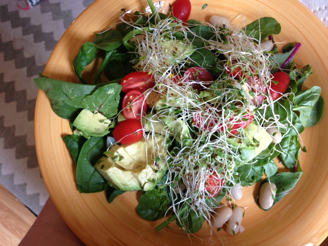 Today's lunch: spinach, baby chard, white beans, half an avocado, grape tomatoes and alfalfa sprouts. Taking a break from my shift at the gym for the delicious sunny salad. Next time I'll add some walnuts for protein!