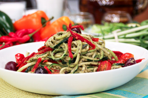 "Warm/Cold Zucchini Noodles With Pesto Ingredients Pesto 1/2 cup walnuts 1 tbsp hemp seeds *optional (sunflower seeds, sesame seeds and chia seeds are also good options).  2 cups fresh basil 3 cloves garlic 1/2 cup extra-virgin olive oil 1 tsp sea salt ""Pasta"" 4 medium-sized zucchini or yellow summer squash 3/4 cup grape tomatoes, sliced in half 3/4 cup olives, pitted 1/2 cup sun-dried tomatoes (not packed in oil), shredded Directions For the pesto, add walnuts, seeds*, basil, garlic, olive oil and salt to a food processor or blender. Process until well combined.  Cut ends off zucchini. You can use a spiralizer (like this one) to make the noodles, or a mandolin to slice the zucchini lengthwise and/or a knife. Try to keep slices thin.  If cold: Toss zucchini pasta with remaining ingredients and pesto, to taste. If warm: Toss noodles very gently in a medium saucepan with 1 tbsp of olive oil for 2-4 minutes over medium heat. Add in pesto, and toss until heated. Serve.  Recipe via CBC"