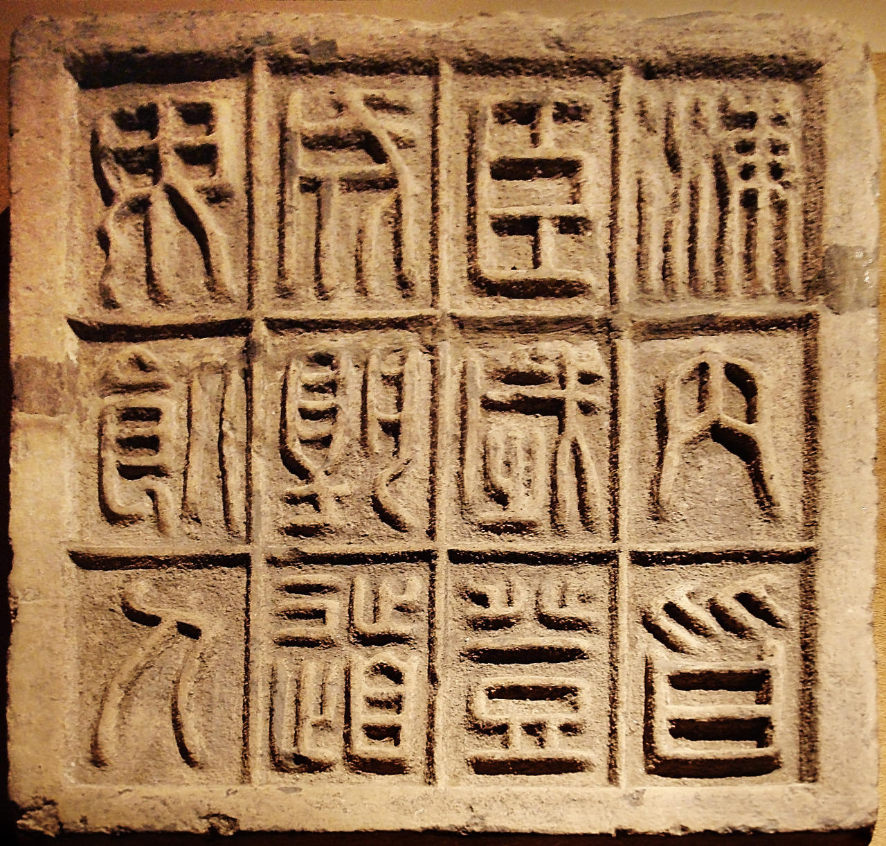Ancient Chinese Stone slab with twelve small seal characters, Qin Dynasty (221 - 206 BC). The 12 characters on this slab of floor brick affirm that it is an auspicious moment for the First Emperor to ascend the throne, as the country is united and no men will be dying along the road. Small seal scripts were standardized by the First Emperor of China after he gained control of the country, and evolved from the larger seal scripts of previous dynasties. Photo taken by Editor at Large at the Treasures of Ancient China exhibit, Canadian Museum of Civilization.