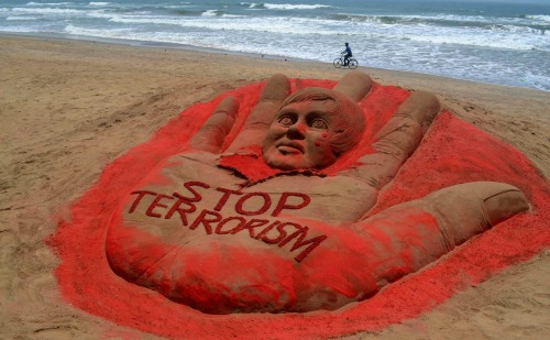 nationalpostphotos:  Sand sculpture against terrorism — A cyclist pedals past a sculpture with a message against terrorism, created after attacks in Boston and Bangalore, at the golden sea beach in Puri, India, Wednesday, April 17, 2013. (AP Photo)
