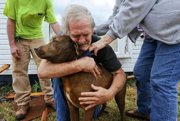Man hugs his dog after they found the dog in the rubble in the aftermath of the Oklahoma Tornados