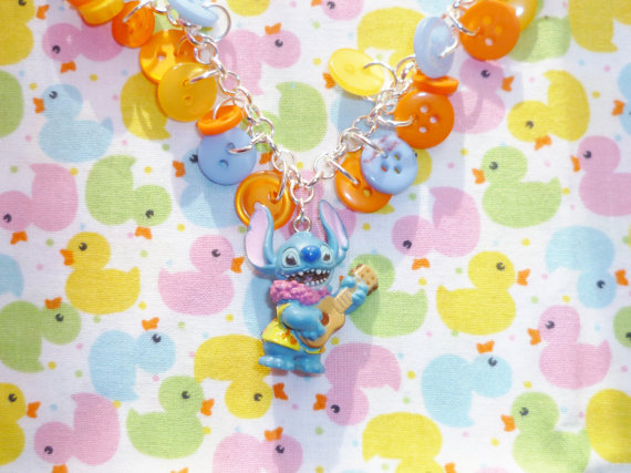 ninefruitspie:  Hey Stitch - Orange, Blue and Yellow Button Charm Necklace with Hawaiian Stitch Charm - £5.50