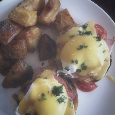 classic eggs benedict with poached eggs, ham, tomatoes, caramelized onions, topped with hollandaise and served with potatoes (at Mission Beach Cafe)