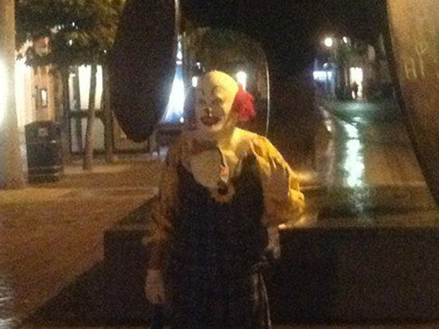 """Mysterious clown terrifying city — and gaining online fame — with unexpected appearances A mysterious man calling himself the """"Northampton Clown"""" is freaking out Northampton, England. Dressed much like the clown Pennywise from the Stephen King novelIt,the clown is fond of standing creepily and updating hisFacebook page, """"Spot the Northampton Clown."""" """"For those of you with phobias and fears, you don't have to like and comment on this page. See you around soon,"""" The Northampton Clown wrote on the page. It's filled with photos culled from social media, showing the clown lurking in a variety of dark corners around Northampton,just over 100 kilometres northwest of London. (Photo: Facebook)"""