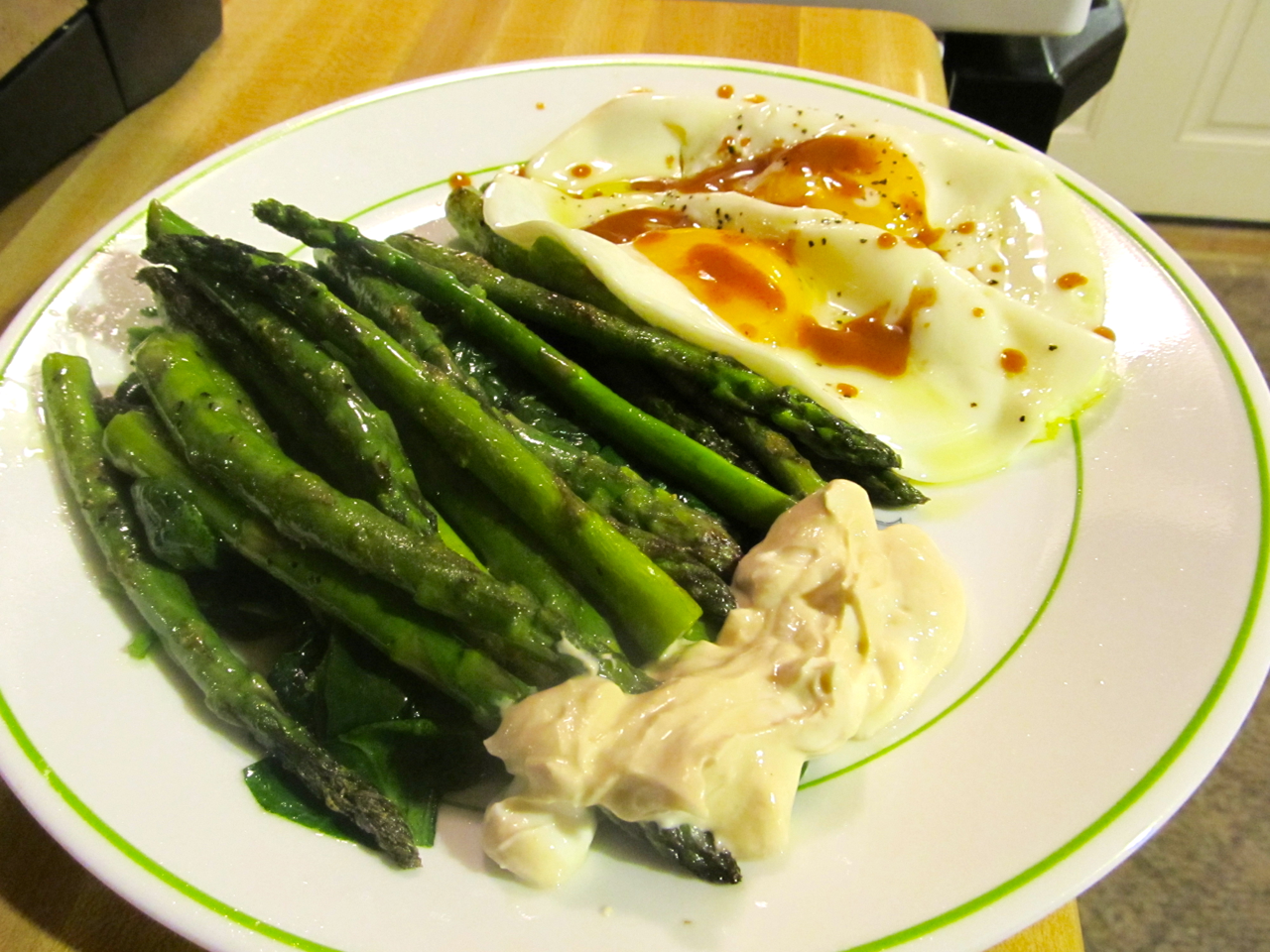 Eggs with enchilada sauce and sautéed asparagus and spinach with yogurt, mustard, and soy dressing