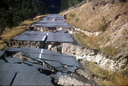 Hebgen Lake, Montana, Earthquake August 1959. Close-up of fractured Highway 287: man inspecting damage.