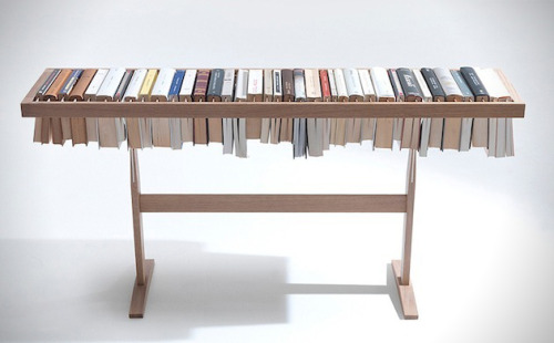Booken  Book Storage Table; not only is the structure made of books placed horizontally, but their draped areas also serve as place holders for the page you left off on.