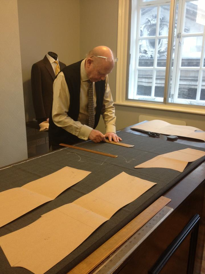 anuntitledaddress:  A Cutter Plying his Craft My tailor (more correctly known as the cutter) is an interesting individual — he's very quiet and half the time, he doesn't understand what I'm talking about (probably in large part because I speak too quickly and have an accent, and in general, cutters don't speak much with clients). But he's been cutting at famous Savile Row houses (past and present) all his life, and was a head-cutter and director at a couple of prominent firms, and if only I had an opportunity to pick his brains and romanticize about the past, I would. Having dressed politicians and aristocrats, I'm sure he has interesting stories to tell, but it's sad that, as matter of tradition, it's not decorous to reveal such intimate details about one's clients. Tailors on the Row are tight-lipped about whom they've dressed. Here, he is about to cut the mid-grey cloth (a H Lesser 11/12 oz Prince-of-Wales self-check), that will eventually be turned into a double-breasted number. This is my third coat with him, and counting.  Those brown 'sheets of paper' are known as a paper pattern, and roughly comprise the constituent parts of a coat, that have been cut to my body measurements. Using this pattern allows for a more consistent and accurate fit, and is, over the course of time, adjusted according to my weight and shape fluctuations. Patterns are usually kept for the duration of the customer's life, and in the case of more notable individuals, are retained even after.