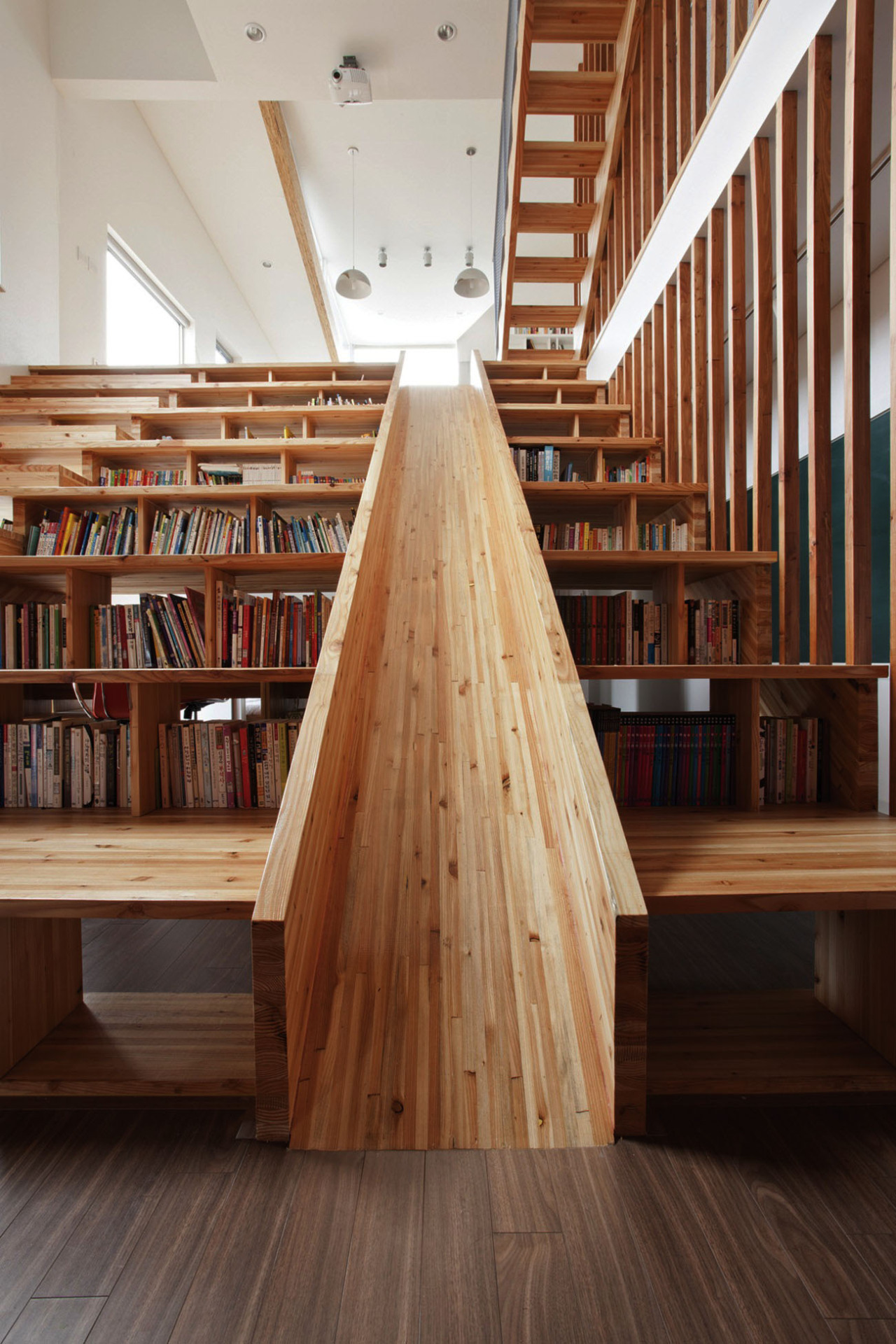 wordpainting:  bookshelfporn:  A Library Slide We love this wooden slide that is slotted into a combined staircase and bookshelf of a house in Chungcheongbuk-do, South Korea, Designed by Moon Hoon. Submitted by Bookshelf Porn reader Jesse Richardson via Colossal.