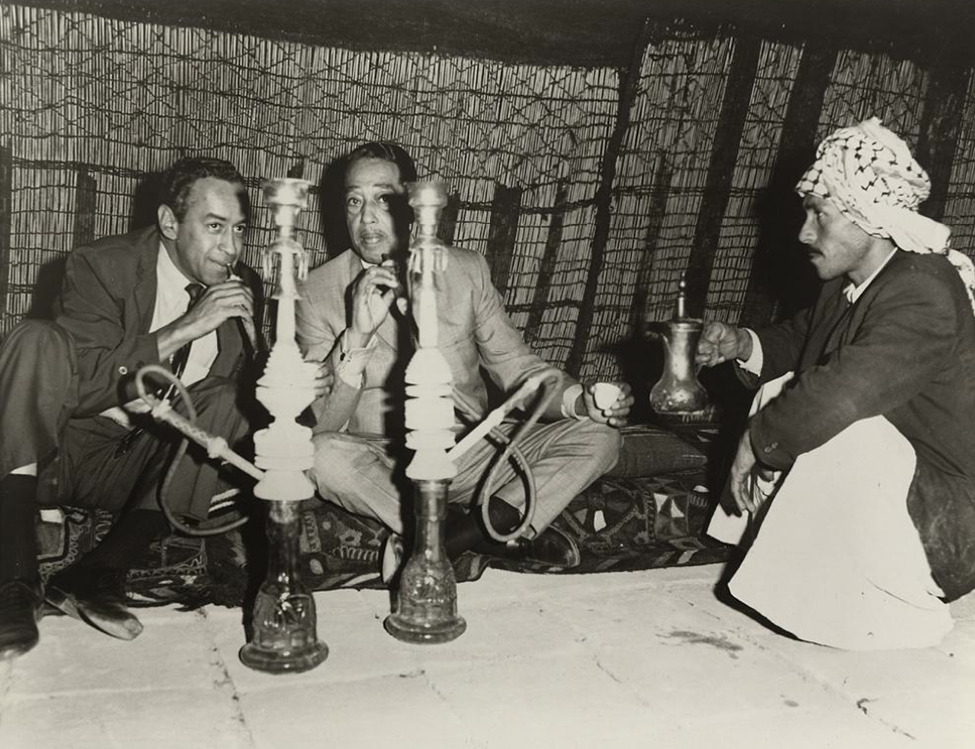 "Duke Ellington With Hookah and Tea in Iraq Edward Kennedy ""Duke"" Ellington, born April 29, 1899 in Washington, D.C., was a global giant in jazz for more than 50 years. As a cultural ambassador, Ellington garnered global recognition for jazz as an original American art form and was admired by fans and heads of state, worldwide, for his artistry. Over the years, Washington, D.C. has celebrated its native son with numerous honors including a community-building contemporary art mural, the development of the Duke Ellington School of the Arts, a statue of Ellington at the piano in front of the legendary Howard Theater and the dedication of a park in his name in the Foggy Bottom neighborhood. But perhaps two of the city's best tributes to Ellington was the installation of the Duke Ellington Collection—an archival treasure trove of photographs, records and other materials, including 100,000 sheets of unpublished Ellington music at the Smithsonian National Museum of American History's Archives Center, and the establishment, through federal appropriation, of the Smithsonian Jazz Masterworks Orchestra as ""the nation's jazz orchestra"" to preserve and disseminate Ellington's jazz legacy and that of other jazz legends, to the nation and the world via tours, recordings, education, and concerts. - Continue reading at Smithsonian.com. Photo courtesy of Duke Ellington Collection, Archives Center, National Museum of American History"