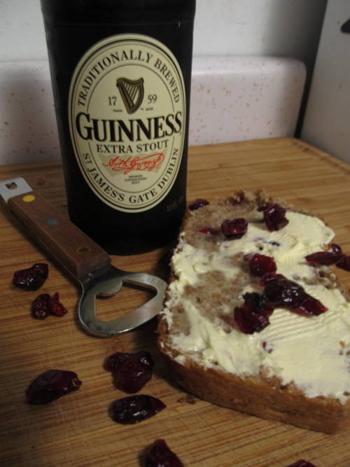 Guinness and Cranberry Oat BreadA Hello-Delicious! Original Recipe Ingredients:1/2 cup Warm water (110 degrees Fahrenheit- no hotter)4 Tbsps + 1 Tbsp packed Dark Brown sugar (divided)1/2 Tsp  granulated white sugar3 tbsp active dry yeast1 tbsp extra virgin olive oil1/2 cup white flour1 and 1/2 cup bread flour1 12 fl. oz bottle of Guinness Extra Stout beer in glass1 tbsp cinnamon1 tbsp Ground Ginger1 tbsp AllspiceA Handfull or two of Ocean Spray dried cranberries1/3 cup organic quick oats Directions:In a small bowl, combine the warm water, tbsp packed dark brown sugar, and 1/2 tsp of granulated white sugar. Mix, and add the 3tbsp of yeast. Let sit 10 minutes to proof. Sift the white flour and bread flour into a bowl, add cinnamon, ginger, and all spice. Mix and add the oats, cranberries, and olive oil, plus the remainder of the brown sugar. Mix thoroughly. Once yeast is wholly activated, add to mixture and mix in. Open the Guinness, and poor in about half the bottle at first. Knead bread and add more Guinness as necessary until the dough is a very wet, sticky consistency. Alternate adding small amounts of white flour and Guinness until almost all of the Guinness is gone (when mine reached the consistency I wanted, I had about from the tip of my finger to the first knuckle's amount left of Guinness in the bottom of the bottle) and the dough has taken on a still stick and moist, yet elastic consistency. Flour a cutting board and roughly flatten the dough. Roll it up on itself until you have a tube. Spray the inside of a glass bread or loaf pan generously with Pam or another cooking spray. Place the tube loaf in the pan (you may have to readjust it a couple times until you roll it into a size that fits properly. Don't stick the bread IN the pan with the spray though until you've rolled it into a size that fits). Cover and allow to rise for 3-5 hours or until the dough has completely filled the bread pan and has a nice top on it. Preheat oven to 200 degrees farenheit towards the last 20 minutes of rising. Once bread is fully risen, bake it in the over at 200 degrees for about 45 minutes. When the bread is done, the outter crust should be a nice deep golden brown, and the bread should sound hollow when tapped. Remove the loaf from the dish, and allow to cool. Note: This is a slightly stickier and certainly a more dense bread than most of my other recipes. 1. It may take longer than 3-4 hours to rise. 2. You cannot judge whether or not it's wholly done by sticking a knife in it until it comes out clean. The best thing to do it bake the bread for 20 minutes the first time, and then in 10 minute intervals after that until you notice the crust getting hard and turning a deep golden brown like shown in the picture.