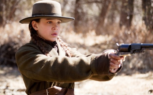 Something about Hailee Steinfeld in True Grit just slays me. I watched the movie last night for what may well have been the fourth time, and every time this has happened, and seemingly with increasing intensity—there are scenes where I find myself on the verge of tears, total lump in the throat and everything, for no apparent reason other than that Mattie Ross, in her hands, is just such a tremendous little badass. But also, she is such a fourteen year old girl. She is a fourteen year old girl as I knew them, as perhaps I was myself—part firecracker, part prude. She knows exactly what she wants, occasionally somehow knows how to get it, but is still living in the fantasy world of late-childhood. Her conversations with Little Blackie are where you really see this, where she seems just like another little girl telling secrets to her horse—the horse she's riding through Indian territory along with a strange drunk U.S. Marshall who she's hired to kill the man who killed her father (and who, in fact, she will eventually kill herself). She knows just enough to be dangerous, the rest patched together with pluck and sass and dumb luck. Also, those braids.