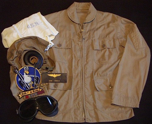 USNR Ensign L. D. Houser's  1940's US Navy flight jacket, cloth helmet, M-1944 goggles, leather name tag, WW2 ribbon bar, silk fliers scarf and Composition Squadron 66 patch. L.D. Houser enlisted in the US Navy in 1943 served first as a air crew gunner on a torpedo diver plane, and later as a commissioned offer and TBD pilot.