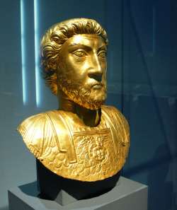 ancientart:  Ancient Celtic bust of Marcus Aurelius, dates to about 180 AD, from Avenches, Switzerland. Through his portraits, the emperor is constantly in attendance over his vast empire. The hair is combed back from the forehead, representing a typical Celtic hairstyle and reveals the Gallo-Roman origin of the artist. Hammered from a single sheet of gold, the bust is a masterpiece of craftsmanship. Courtesy & currently located at the Historical Museum of Bern. Photo taken by Xuan Che   This is a really good example of art from the Roman provinces. The Celtic influences in the sculpture are unmistakable yet the subject matter couldn't be anymore Roman. A process of Romanization? Or a new hybrid-style of artwork?