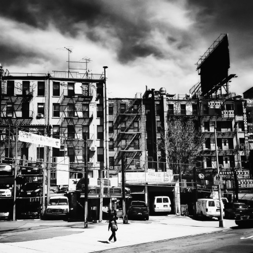 "Storm clouds and tenements. Chinatown, New York City.  As storm clouds approach, the sun washes over the city showering its splendor onto the urban landscape like a brilliant star projecting its last bits of light into the vast universe.  —-  I love the light on the buildings in this section of Chinatown before a storm. This particular view overlooks the tenements that face the Forsyth Market under the Manhattan Bridge where produce and other food is sold daily in a sprawling open air market.  —-  View this photo larger and on black on my Google Plus page —-  Buy ""Storm Clouds - Chinatown - New York City"" Posters and Prints here, email me, or ask for help."