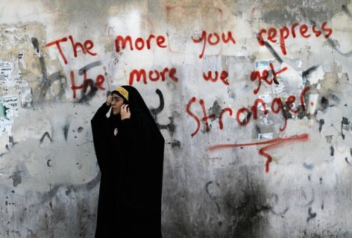 fotojournalismus:  A Bahraini anti-government protester watches riot police, unseen, during clashes in Diraz, Bahrain on May 6, 2013. Large numbers of riot police stormed the area just ahead of a planned demonstration in support of jailed activists, chasing away demonstrators as they arrived for the march. [Credit : Hasan Jamali/AP]