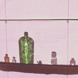 Bottles and a waving monkey behind a window shade