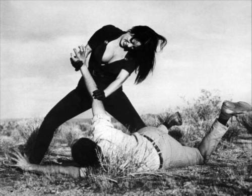 "Tura Satana was a Japanese-Scots-Irish-Native American actress and former dancer. At school she was constantly harassed for her large breasts and asian appearance, and at the age of 9 she was gang raped by 5 men walking home from school. None of her attackers were prosecuted (the judge was reportedly paid off) so Tura took it in her stride to take up martial arts and learnt Aikido and Karate and over the next 15 years tracked down each rapist and extracted her own revenge.  Not even a stint in reform school could stop this woman, she became the leader of a gang she started with the other students and in her words they ""had leather motorcycle jackets, jeans and boots and kicked butt."" She played Varla in Russ Meyer's ""Faster Pussycat! Kill! Kill!"" in which she did all her own stunts and improvised most of the films best lines including a scene when a gas attendant stares at her breasts and says how he'd like to travel America to which Varla replies ""You wont find it down there Columbus.""   Bad Bitch Ambitions"