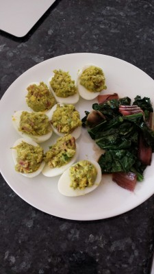 Deviled eggs with avocado and bacon. Side of chard and kale