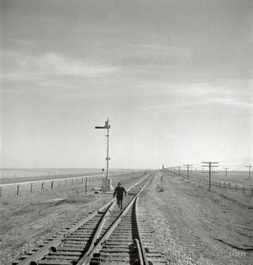 "(via A Fork in the Railroad: 1943 | Shorpy Historical Photo Archive)  March 1943. ""Sumnerfield, Texas. Brakeman running back to his train on the Atchison, Topeka & Santa Fe Railroad between Amarillo, Texas, and Clovis, New Mexico, as it is ready to start again, after having waited in a siding."" Photo by Jack Delano for the Office of War Information. View full size."